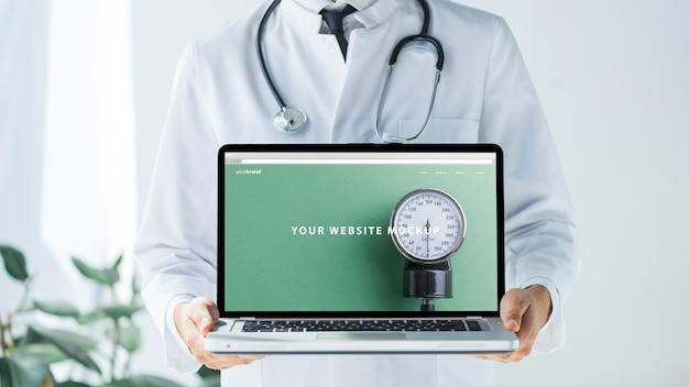 Doktor, der Laptopmodell für Website hält Kostenlose PSD