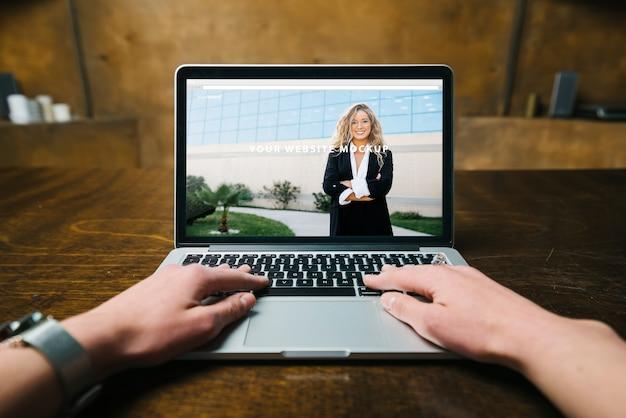 Laptop-Modell mit den Händen Kostenlose PSD