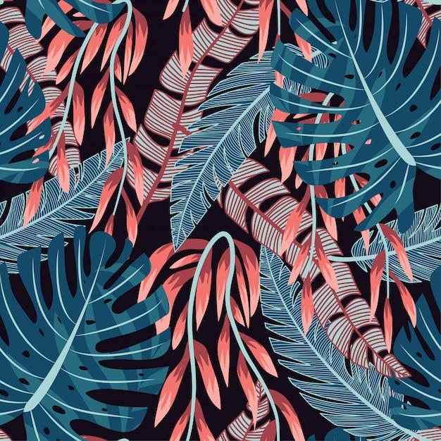Abstrait brillant modèle sans couture avec des feuilles tropicales colorées et des plantes sur fond noir Vecteur Premium