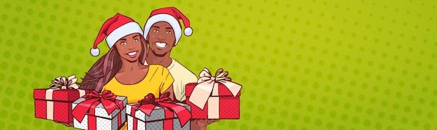 Afro-américain, Couple, Porter, Chapeaux Santa, Tenue, Présente, Heureux, Homme, Femme, Bannière Horizontale Vecteur Premium