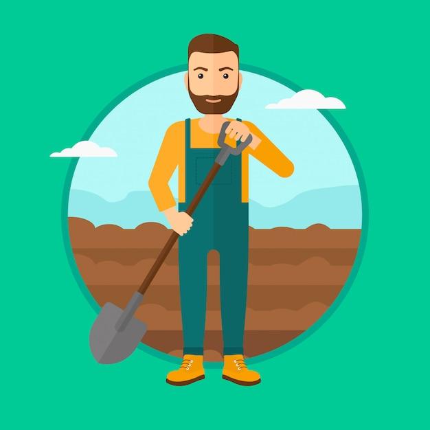 Agriculteur sur le terrain avec une pelle. Vecteur Premium