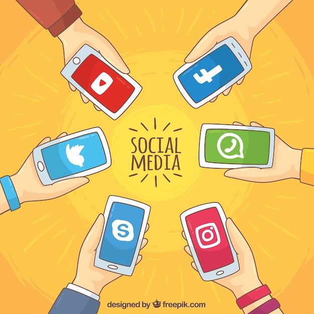 Arrière-plan de mains tenant les téléphones mobiles avec les réseaux sociaux Vecteur gratuit