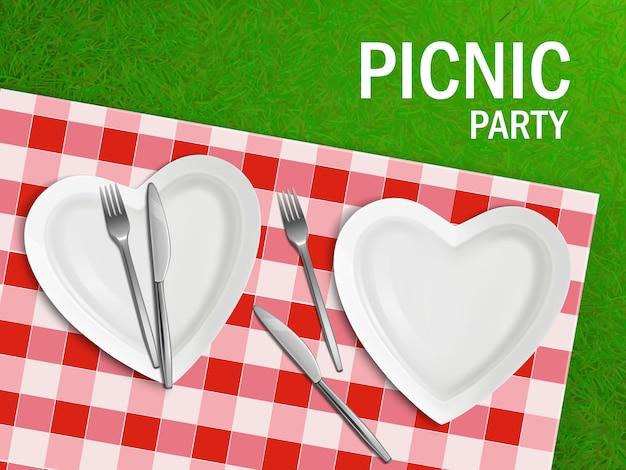 Assiette en forme de coeur sur la nappe et l'herbe verte Vecteur gratuit