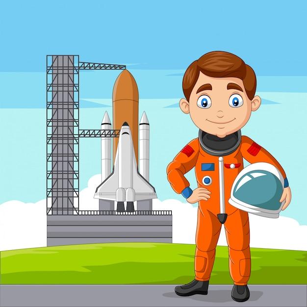 Astronaute de dessin animé tenant un casque avec le vaisseau spatial prêt à lancer Vecteur Premium