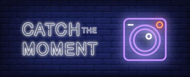 Attrapez l'illustration du moment dans un style néon. texte et caméra sur fond de mur de brique. Vecteur gratuit