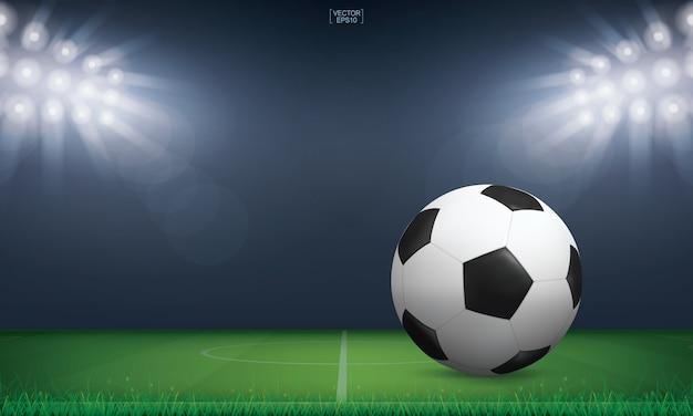 Ballon de football sur l'herbe verte du terrain de football. Vecteur Premium