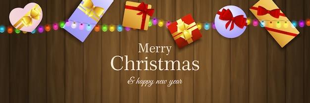 Bannière de joyeux noël avec des cadeaux sur un sol en bois brun Vecteur gratuit