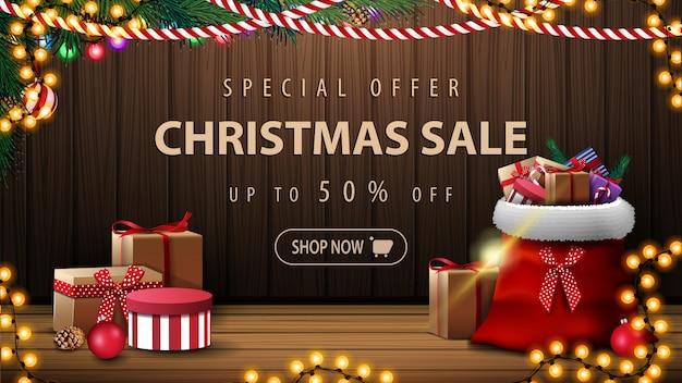 Bannière de vente joyeux noël avec sac du père noël avec des cadeaux et mur en bois avec décor de noël Vecteur Premium