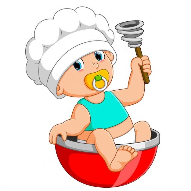 Le bébé chef est assis sur l'arc rouge et tient un batteur manuel Vecteur Premium