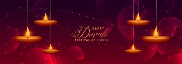 Belle bannière brillante de joyeux diwali avec pendaison de diya Vecteur gratuit