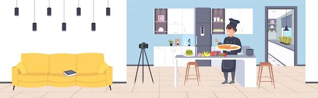 Blogueur Alimentaire En Uniforme Cuisson Pizza Dans La Cuisine Mâle Chef Enregistrement Vidéo Blog Avec Caméra Sur Trépied Blogging Concept Homme Vlogger Expliquant Comment Faire Cuire Un Plat Horizontal Pleine Longueur Vecteur Premium