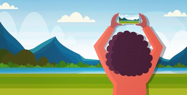 Blogueur De Voyage à L'aide De L'appareil Photo Du Smartphone Pendant La Randonnée Femme Prenant Des Photos Ou Des Vidéos En Direct En Streaming Concept Wanderlust Montagnes Paysage Fond Portrait Horizontal Vecteur Premium