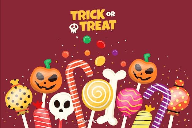 Bonbons sur fond plat d'halloween Vecteur gratuit