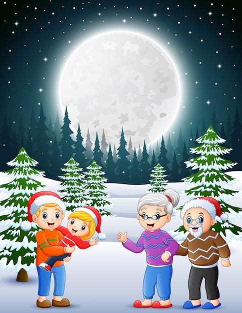 Bonne famille dans le jardin enneigé la nuit Vecteur Premium