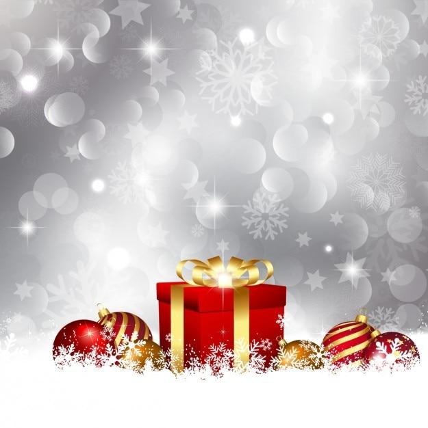 Cadeau rouge avec des boules sur le fond de neige Vecteur gratuit