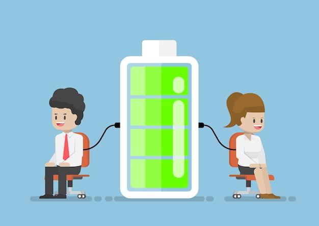 Caractère D'homme D'affaires Et De Femme D'affaires Chargeant L'énergie De La Batterie Vecteur Premium