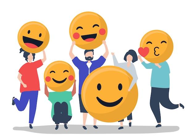 Caractères des personnes tenant une illustration d'émoticônes positives Vecteur gratuit