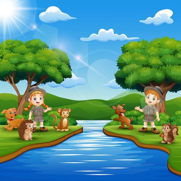 Caricature de zookeeper garçon et fille avec animal au bord de la rivière Vecteur Premium