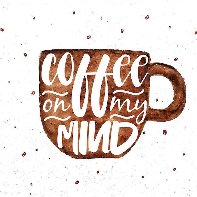 Carte de lettrage avec une tasse à café brune aquarelle Vecteur Premium