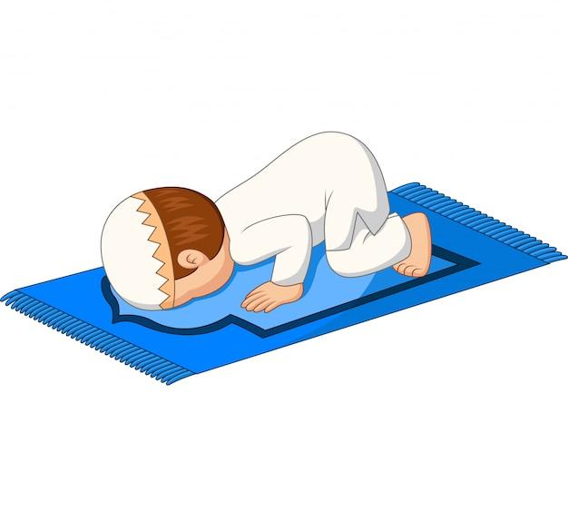 Cartoon musulman garçon prière s'incliner sur le tapis Vecteur Premium