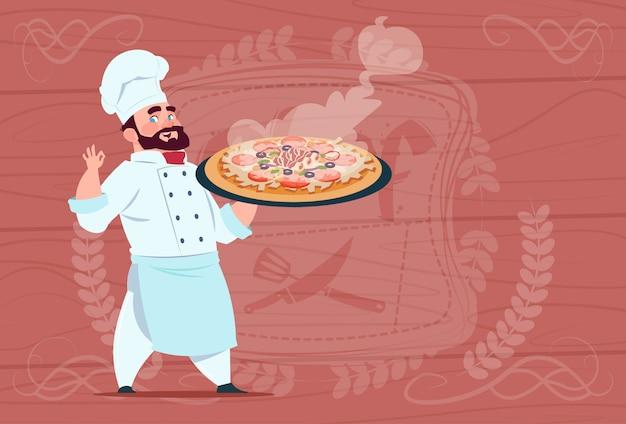 Chef cuisinier tenant pizza chef de bande dessinée souriant en uniforme de restaurant blanc sur fond texturé en bois Vecteur Premium