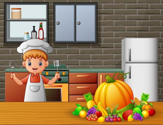 Chef garçon tenant une spatule et une fourchette dans la cuisine Vecteur Premium
