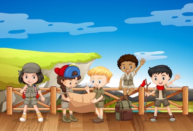 Cinq enfants en tenue de safari debout sur le pont Vecteur gratuit