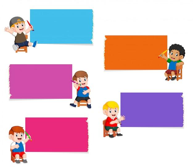 La collection du tableau blanc dans la couleur différente avec les enfants tenant la peinture au pinceau Vecteur Premium