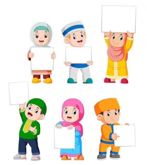 Collection d'enfants musulmans tenant une grande pancarte blanche Vecteur Premium