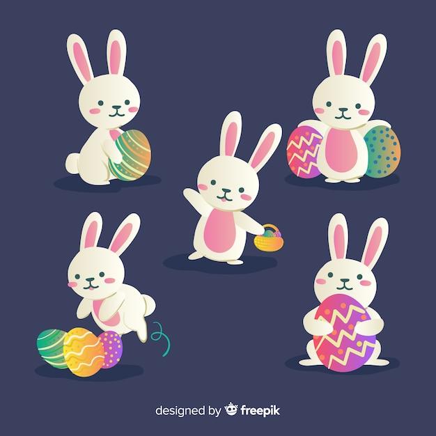 Collection de lapin de pâques dessinés à la main avec des oeufs Vecteur gratuit