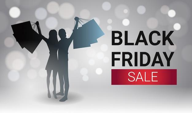 Conception de bannière vente vendredi noir avec couple silhouette tenant des sacs à provisions sur white lights bokeh Vecteur Premium