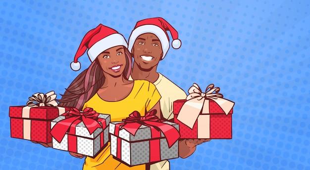 Couple Afro-américain Portant Des Chapeaux De Père Noël Présente Un Homme Et Une Femme Heureux à Propos De Pop Art Comique Vecteur Premium
