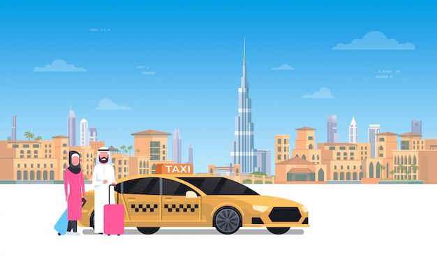 Couple arabe assis dans une voiture de taxi jaune au-dessus de la ville de dubaï Vecteur Premium