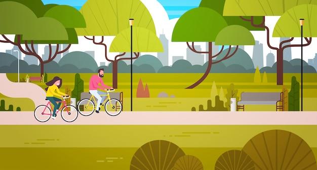 Couple, équitation, vélos, dans, parc public, sur, ville, bâtiment, horizon, homme femme, cyclisme, dehors Vecteur Premium