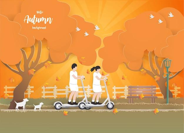 Couple sur un scooter électrique en automne fond. Vecteur Premium