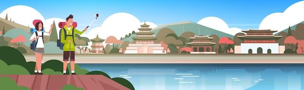 Couple de touristes avec sacs à dos prendre une selfie sur de beaux bâtiments chinois fond homme et femme de randonneurs en asie bannière horizontale Vecteur Premium