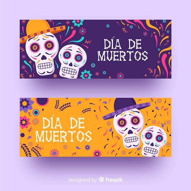 Crânes de día de muertos plats avec des bannières sombrero Vecteur gratuit