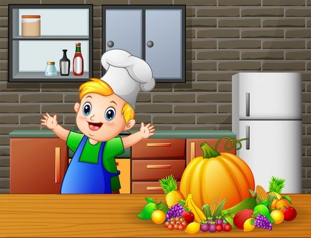 Dessin animé mignon petit garçon en tablier et une toque près de la table à manger Vecteur Premium