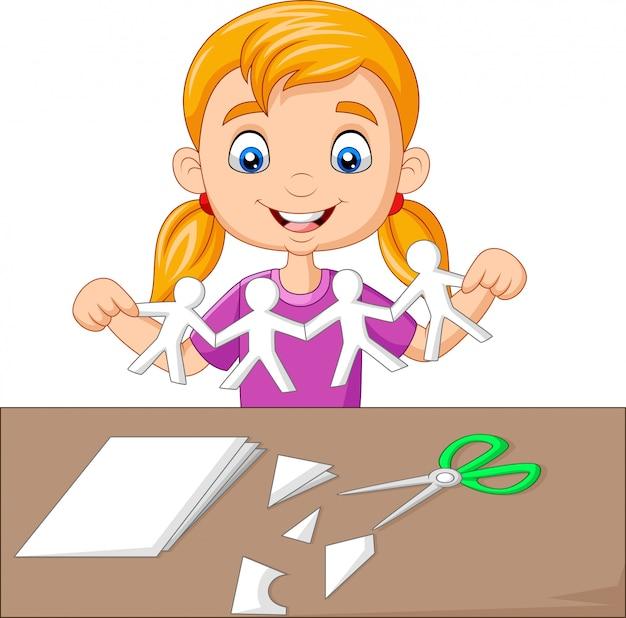 Dessin animé petite fille faisant des gens de papier Vecteur Premium