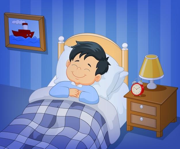 Dessin animé sourire petit garçon dort dans le lit Vecteur Premium