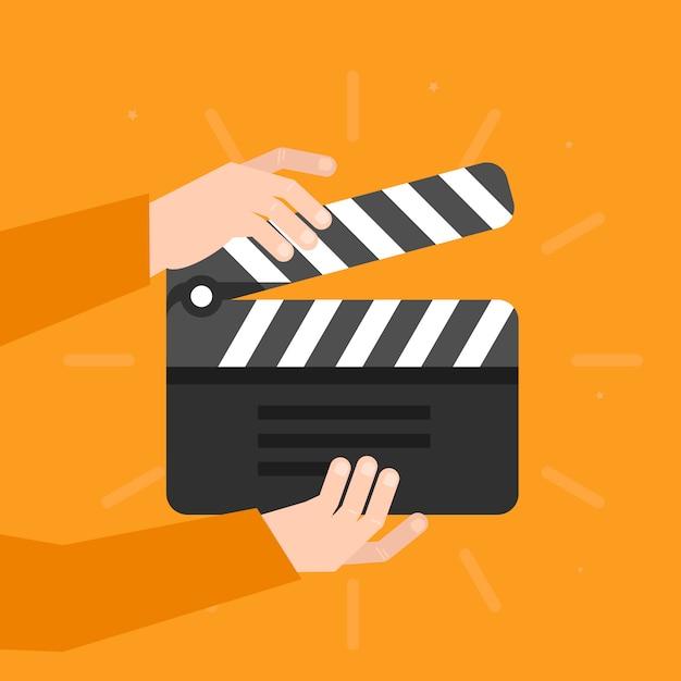 Deux mains tenant un battant de cinéma dans un style plat Vecteur Premium