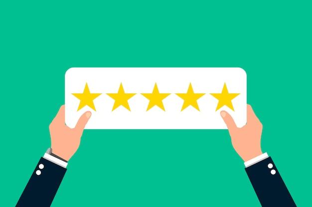 Deux mains tiennent une table avec cinq étoiles sur un fond vert. Vecteur Premium