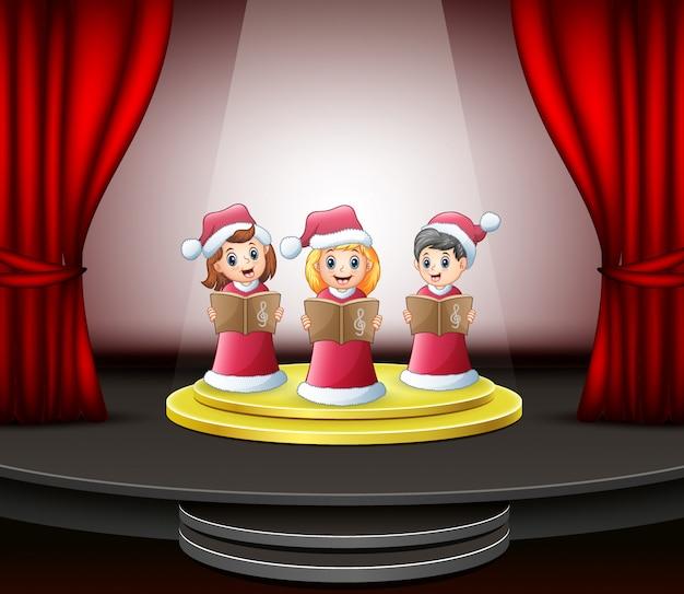 Enfants dessin animé chantant des chants de noël sur la scène Vecteur Premium
