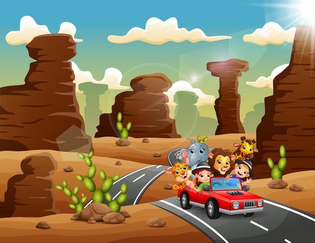 Enfants dessin animé conduisant une voiture rouge avec des animaux sauvages à travers le désert Vecteur Premium