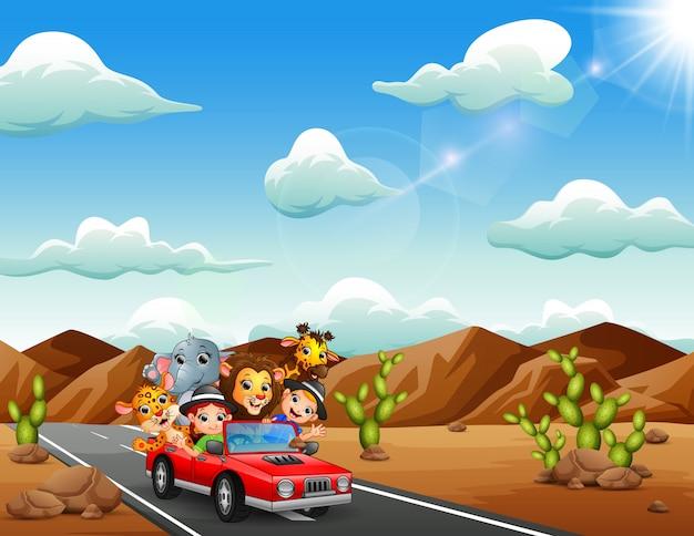 Enfants dessin animé conduisant une voiture rouge avec des animaux sauvages Vecteur Premium