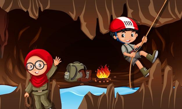 Enfants explorant la grotte Vecteur Premium