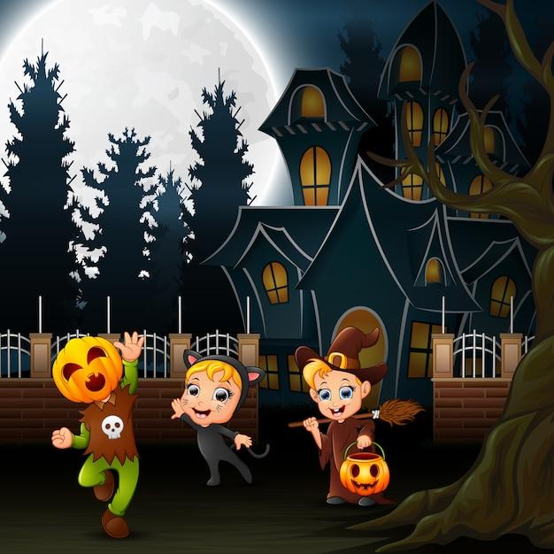 Enfants halloween heureux avec maison effrayante et pleine lune Vecteur Premium