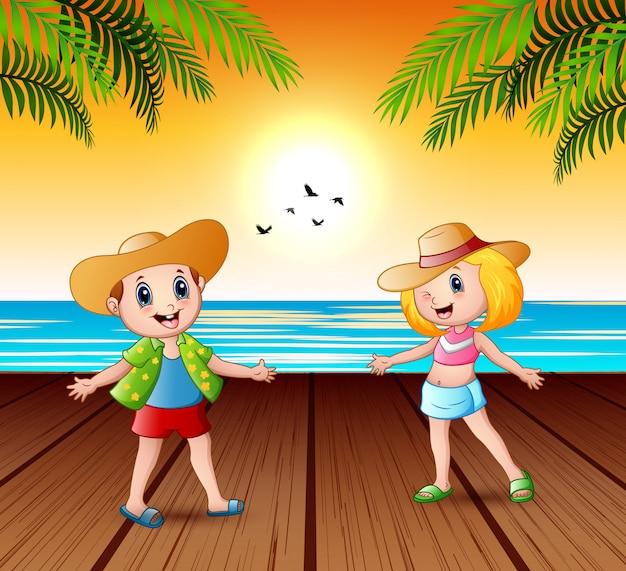 Enfants heureux sur la jetée et à la recherche d'un paysage coucher de soleil Vecteur Premium