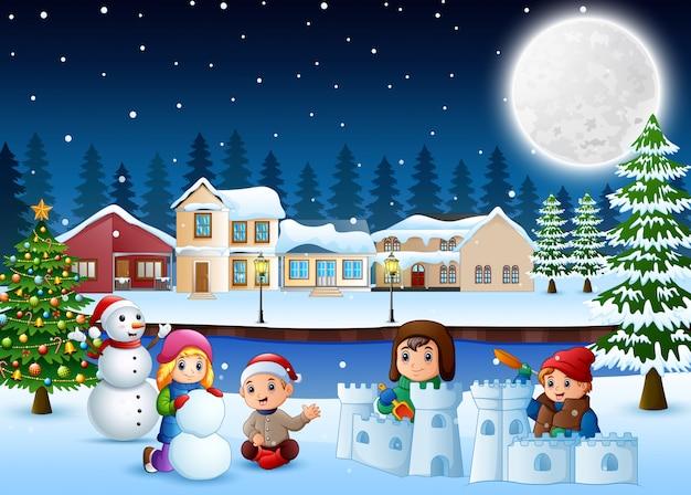 Enfants heureux jouant et faisant une neige en hiver Vecteur Premium
