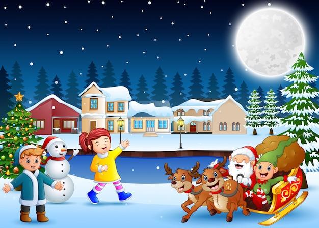 Enfants heureux avec le père noël et elfe sur son traîneau dans la nuit d'hiver Vecteur Premium